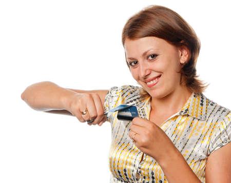 Smiling girl cuts a credit card, refusal of crediting photo
