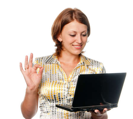 Smiling girl with laptop shows gesture OK photo
