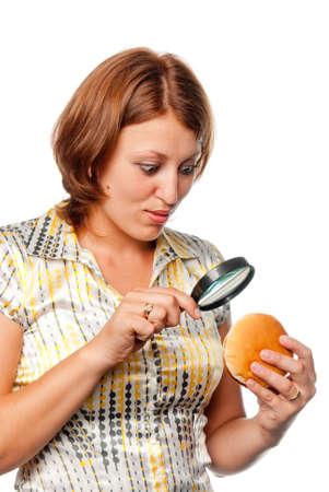 considers: Girl considers a hamburger through a magnifier