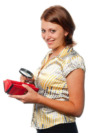 considers: Smiling girl considers a purse through a magnifier
