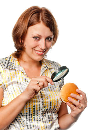 considers: Smiling  girl considers a hamburger through a magnifier Stock Photo