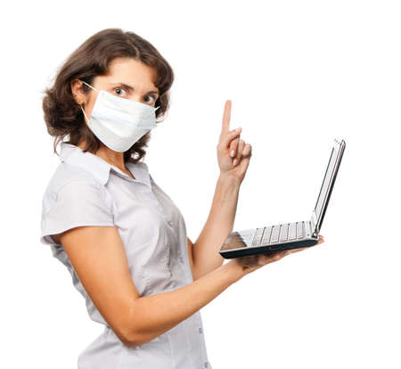 Strict girl in a protective mask with a laptop photo