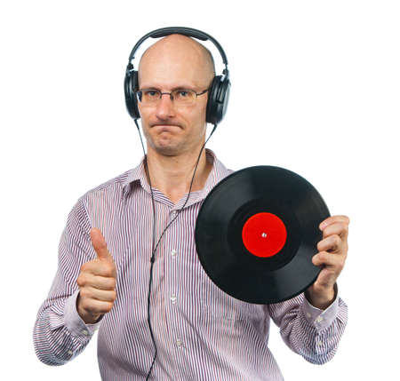 surety: Music lover in headphones shows old music disc Stock Photo