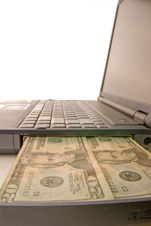 a laptop computer with money coming out of it on white