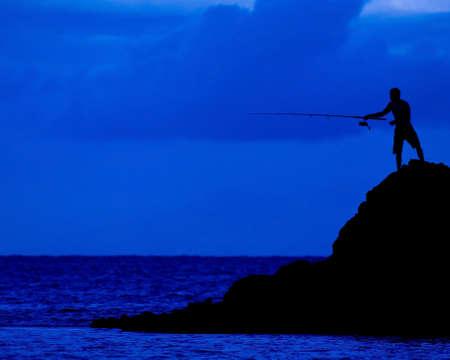 岩から海に釣り人間の暗闇の図