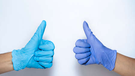 hand in a medical glove shows gesture ok. white background and copy space.