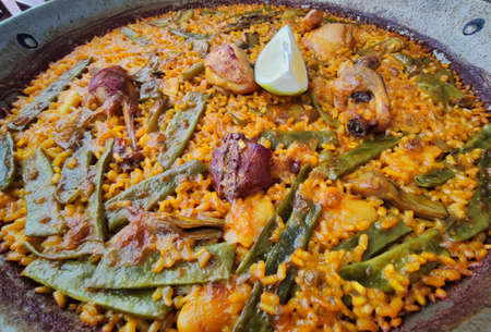 Rich Valencian paella with chicken and rabbit