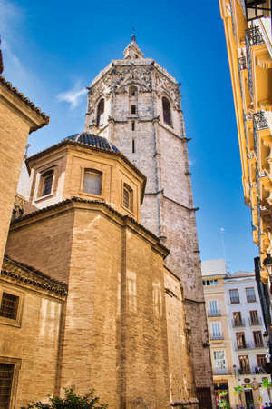 Street and side of the cathedral of Valencia with its bell tower of Micalet 免版税图像