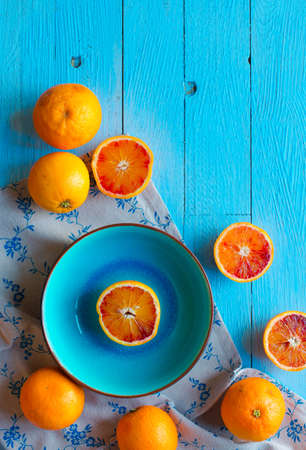 refreshment: Colorful Orange fruits over a light blue painted wood table with a simmetric position.