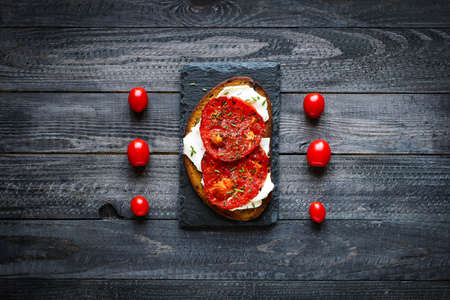 vegetables on white: Delicious Tasty Avocado Eggs and Tomato Cheese Toasts over a stone plate with an old look wooden background and dramatic light.