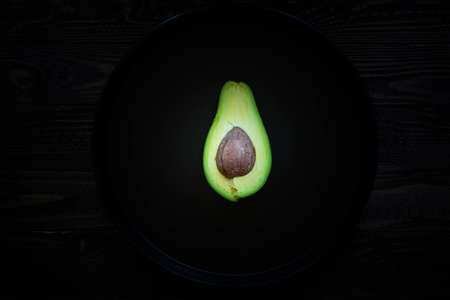 pan tropical: Veggie Food composition with half avocado over a darkdish and a wood distressed old background. Dramatic light.