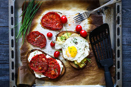 Delicious Tasty Avocado Eggs and Tomato Cheese Toasts over a stone plate with an old look wooden background and dramatic light.