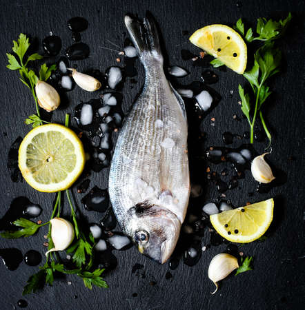john: Fresh Fish Orata Over a Black stone with vegetables, lemon and pieces of ice.