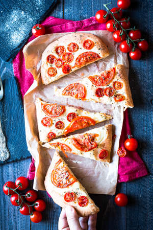mini oven: Tasty Hand Made Tomatoes  Pizza Bread with italian style recipe over a wooden table with a Dramatic light. Stock Photo