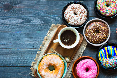 doughnut: Colorful Donuts breakfast composition with different color styles of doughnuts and fresh coffee on the side over an aged wooden desk background. Stock Photo