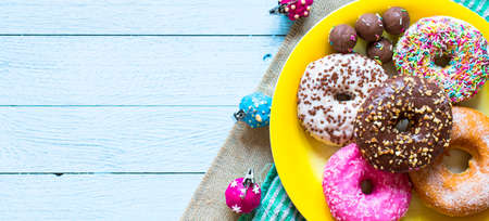 chocolate cakes: Colorful Donuts breakfast composition with different color styles of doughnuts over an aged wooden desk background.