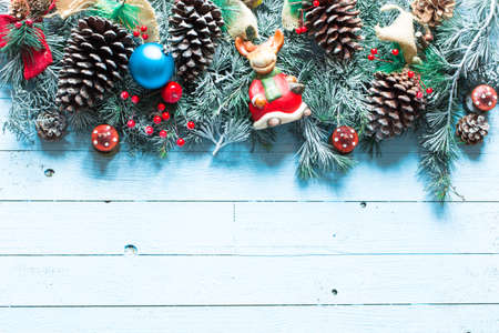stuff: Merry Christmas Frame with real wood green pine, colorful baubles, knots with berries and other seasonal stuff over an old wooden aged background