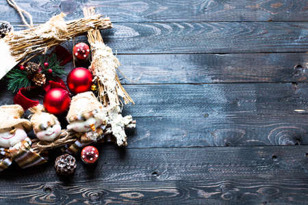 Merry Christmas Frame with real wood green pine, colorful baubles, knots with berries and other seasonal stuff over an old wooden aged background