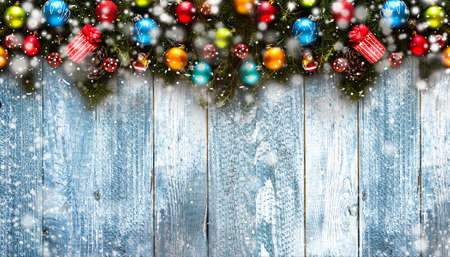 stuff: Merry Christmas Frame with Snow and real wood green pine, colorful baubles, knots with berries and other seasonal stuff over an old wooden aged background