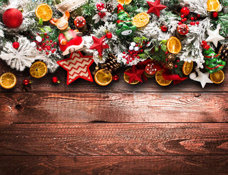 Merry Christmas Frame with green pine, colorful baubles, knots with berries,stars, orangesand other seasonal stuff over an old wooden aged background