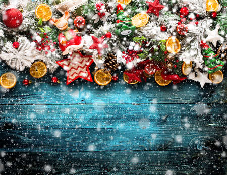 Merry Christmas Frame with Snow and wood green pine, colorful baubles, knots with berries,stars, orangesand other seasonal stuff over an old wooden aged background Stock Photo