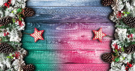 stuff: Merry Christmas Frame with green pine, colorful baubles, knots with berries,stars and other seasonal stuff over an old wooden aged background Stock Photo