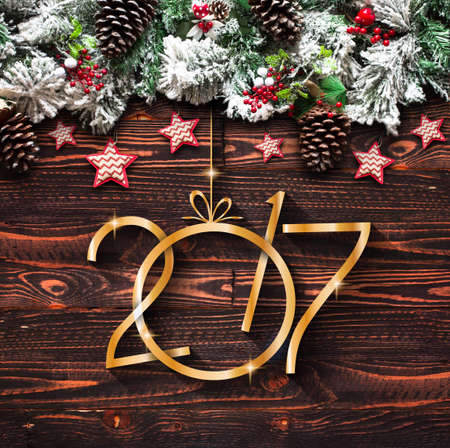 year old: 2017 New Year  Frame with green pine, colorful baubles, knots with berries,stars and other seasonal stuff over an old wooden aged background Stock Photo