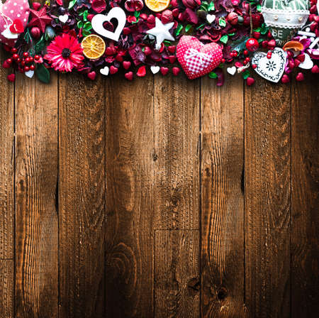 Valentines Day Background with love themed elements like cotton and paper hearts, flowers, berries, oranges and other decorations. Wooden old parquet on the back.