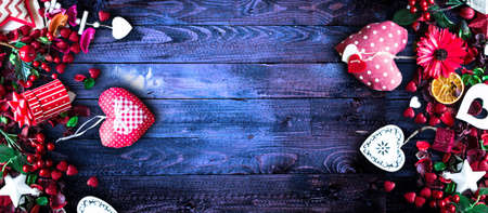 Valentine's Day Background with love themed elements like cotton and paper hearts, flowers, berries, oranges and other decorations. Wooden old parquet on the back.