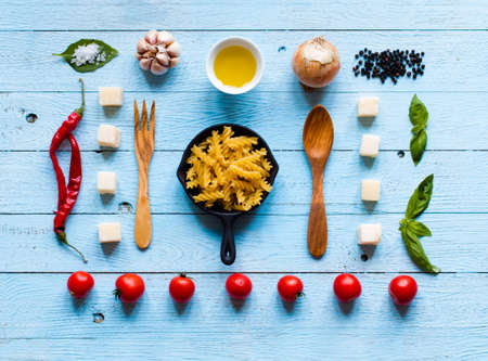 Top view of all the necessary food component to make a classic italian pasta with tomato sauce with basil and olive oil!