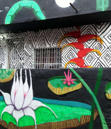 Sao Paulo, Sao Paulo, Brazil; 11222014: Colorful mural of street art about lotus flower, heliconia and amazonian flora with stunning native shapes located in Batman Alley or Beco do Batman, a street with graffiti in Sao Paulo