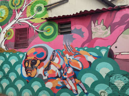 Sao Paulo, Sao Paulo, Brazil; 11222014: Colorful mural of street art  about an abstract water and tree cartoon and a fat man located in Batman Alley or Beco do Batman, a street with graffiti in Sao Paulo Editorial