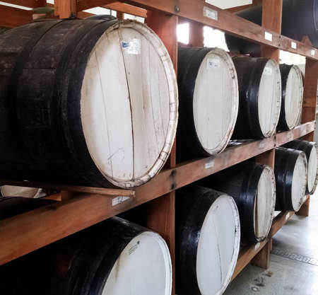 Large black wooden barrels for storage of alcoholic beverages grouped in a cellar shelf. Distilled alcoholic beverage, wine and cachaça industry. Фото со стока