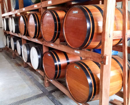 Wooden barrels for storage of alcoholic beverages grouped in a cellar Фото со стока