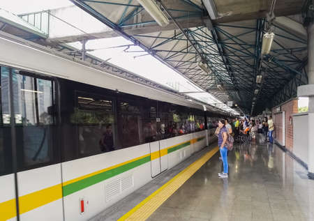 Group of people, passengers, about to board a train of the Medellin Metro.