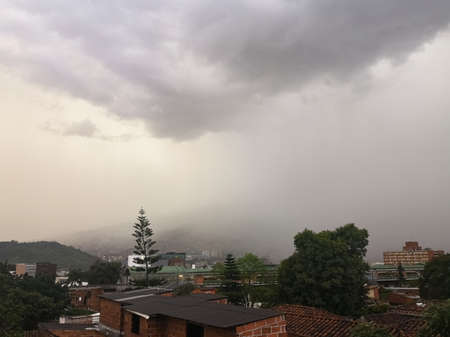 Torrential stormy rain over the Colombian city of Medellin. Gray and cloudy day with isolated rain. Detail of houses, trees and metro system. Editorial