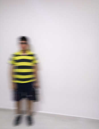 Young man dressed in black shorts with yellow striped shirt defocused and moving with an intentional blur to give a concept of ghost, disappearance, spectrum, action or motion.Young man dressed in black shorts with yellow striped shirt defocused and moving with an intentional blur to give a concept of ghost, disappearance, spectrum, action or motion. Stock Photo