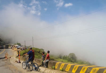 Cyclist and children in a mountain road in Antioquia, countryside Colombia, with a chasm background covered with haze. Concept of periphery and poverty in rural areas.