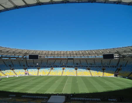 Majestic Maracana Stadium, in the beautiful city of Rio de Janeiro, Brazil. Bright detail of green playing field and sunny blue day.
