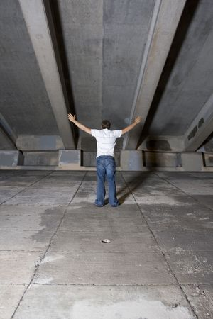 Young white male under an overpass at night with his arms raised