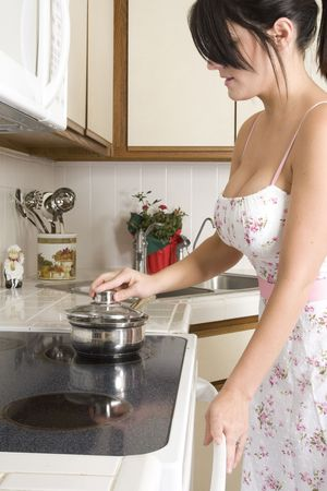 beautiful brunette housewife working in her kitchen Stock Photo - 5316345