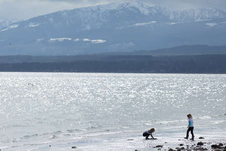 vancouver island: girls playing on a sandy baech near Comox, Vancouver Island, BC, Canada
