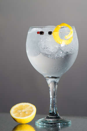 Gin Tonic with lemon and botanics in a balloon glass on grey background. photo