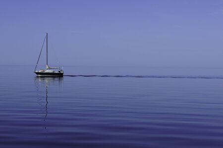 peacefulness: Sailboat sailling without sails on a beautiful and calm day