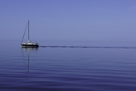 sailling: Sailboat sailling without sails on a beautiful and calm day