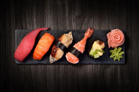 Sushi on black stone slate plate, black wooden background