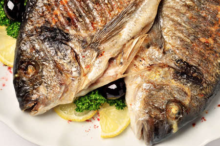 gilthead bream: Grilled Gilt-head bream served with fresh lemon slices, parsley and black olives