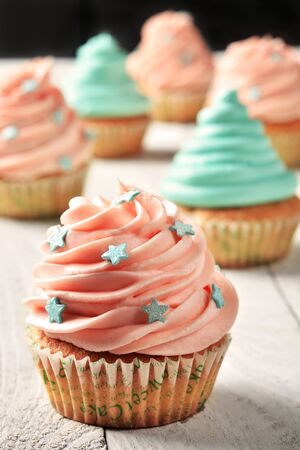 sprinkling: Cupcakes with turquoise and pink cream decarated with star-shaped culinary sprinkling Stock Photo