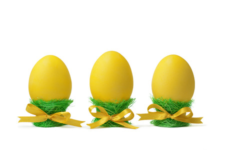 sisal: Three yellow Easter eggs in egg-cups isolated on white background. Egg-cups are made of green sisal.