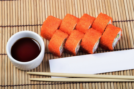 California Maki Sushi set with chopsticks and blank paper wrapper on sushi mat